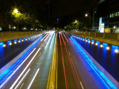 De nuit, certains tunnels bruxellois sont éclairés de lumière d'ambiance. Nous voyons ici le tunnel Art-Loi, illuminé de bleu, et de rouge et blanc/jaune pour les trainées des phares de voitures.