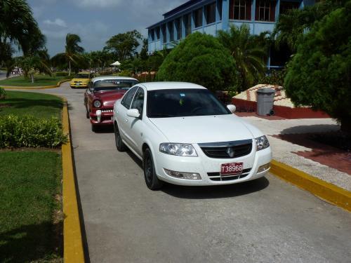 Nous sommes à Guardalavaca, un complexe hôtelier de la Province de Holguín, à Cuba, où cette Renault Scala (aussi commercialisée sous les noms Renault Samsung SM3, Nissan Almera, Nissan Almera Classic, Nissan Bluebird, Nissan Sunny en fonction des marchés) est garée devant une Mercury 1955. Près d'un demi-siècle sépare le début de la production de ces deux voitures...<br /> La Renault est une voiture de location pour les touristes, comme l'indique la couleur de la plaque et la lettre T du début de l'immatriculation.