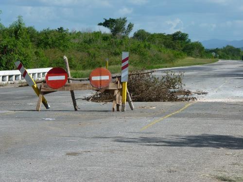 Cette photo illustre bien ce qu'on peut trouver d'insolite sur les routes cubaines, à savoir par exemple un trou signalé par des branchages et une barrière...