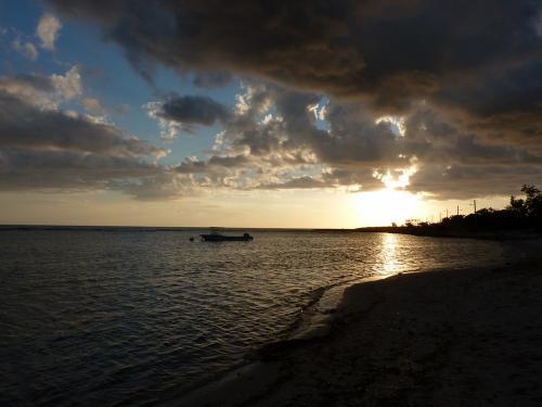 Un coucher de soleil peut être l'occasion de jolies photos. Celle-ci illustre les différentes couleurs qu'on peut avoir, lorsque le ciel, bien bleu, est légèrement couvert par des nuages biens gris, et que le soleil offre des teintes orangées...