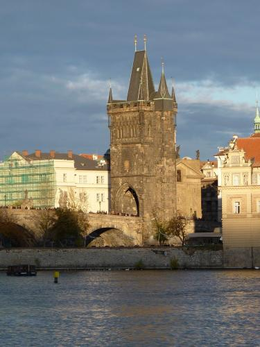 Du côté de la vieille ville (Staré Město), le pont Charles et surmonté d'une tour gothique. Celle-ci est photographiée depuis la rive opposée de la Vltava, dans un décore assez contrasté avec un ciel gris en arrière-plan.